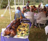 Dressed pig and guests under tent at outdoor wedding